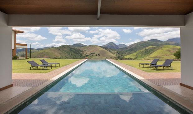 Tijolos, madeira e vidro em uma casa com vista para as montanhas (Foto: Divulgação)