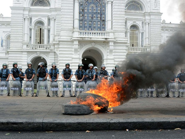 Cordão policial protege prefeitura de La Plata, na Argentina, diante de pneus que pegam fogo durante protesto contra revisão de cargos públicos (Foto: AFP PHOTO/TELAM-CARLOS CERMELE)