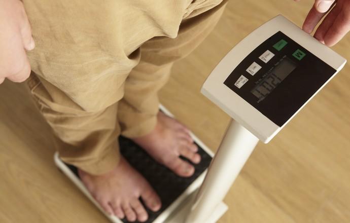Homem se pesando na balança euatleta (Foto: IStock Getty Images)