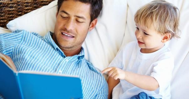 Pai e filho lendo livro juntos no sofá (Foto: Shutterstock)
