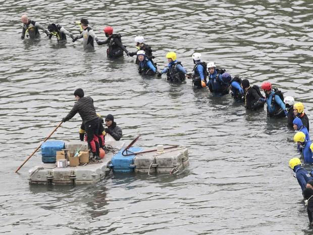 Equipe de resgate faz cordão varrendo trecho de rio em busca de vítimas da queda do avião da TransAsia em Taipei, Taiwan. O acidente do voo 235, com 58 pessoas a bordo, deixou dezenas de mortos (Foto: Wally Santana/AP)