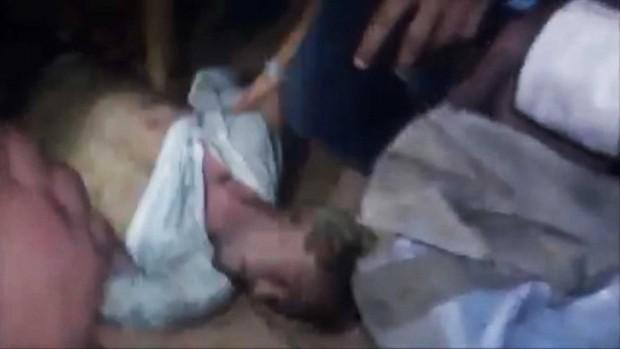 Vídeo amador mostra homens retirando o diplomata Christopher Stevens de uma sala cheia de fumaça (Foto: AP)