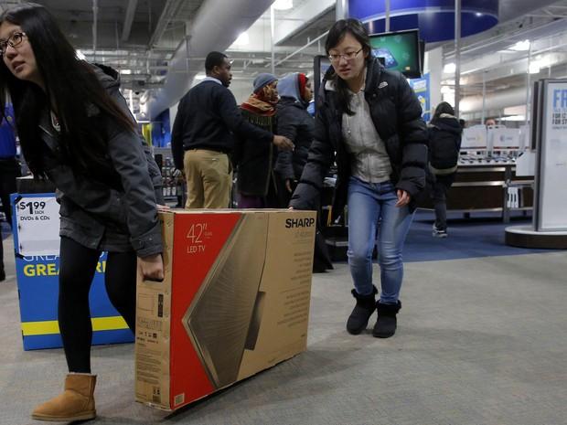 Duas mulheres arrastam uma televisão recém comprada em Cambridge, Massachusetts durante o Black Friday. (Foto: Brian Snyder/Reuters)
