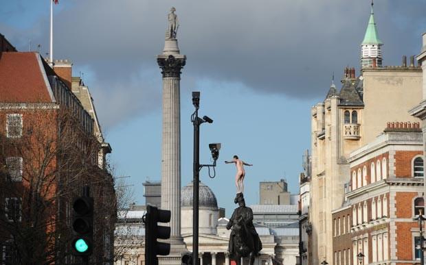 Homem não identificado ficou duas horas nu sobre estátua em Londres nesta sexta-feira (23) (Foto: Stefan Rousseau/PA/AP)