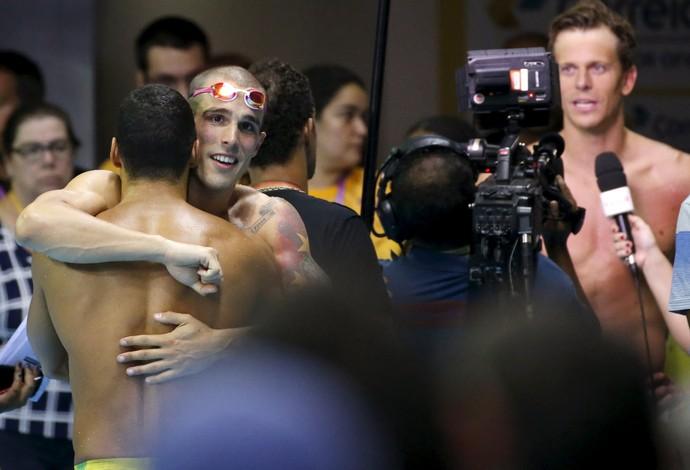Bruno Fratus e Ítalo Manzine se abraçam enquanto Cesar Cielo concede entrevista (Foto: Reuters)