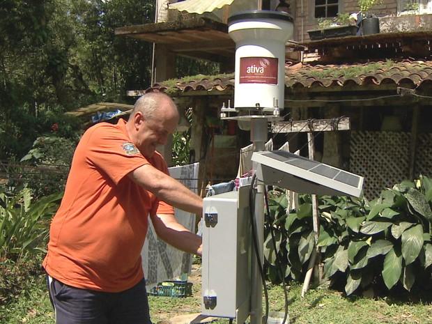 Chefe da Defesa Civil de São Sebastião ajusta pluviômetro usado no monitoramento.  (Foto: Reprodução/TV Vanguarda)