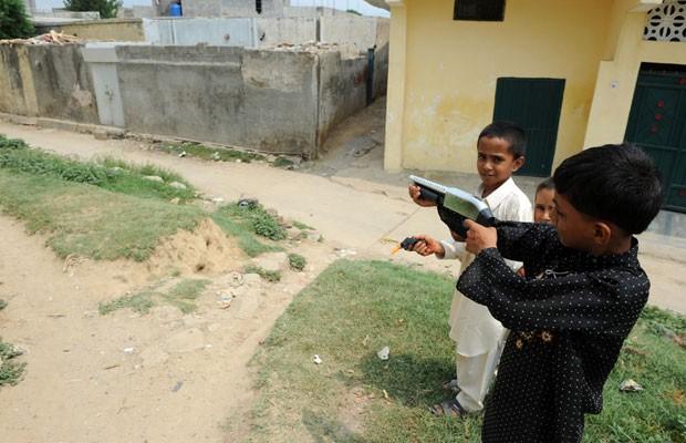Crianças brincam com armas de brinquedo perto da casa da menina presa por queimar o Alcorão (Foto: AFP)