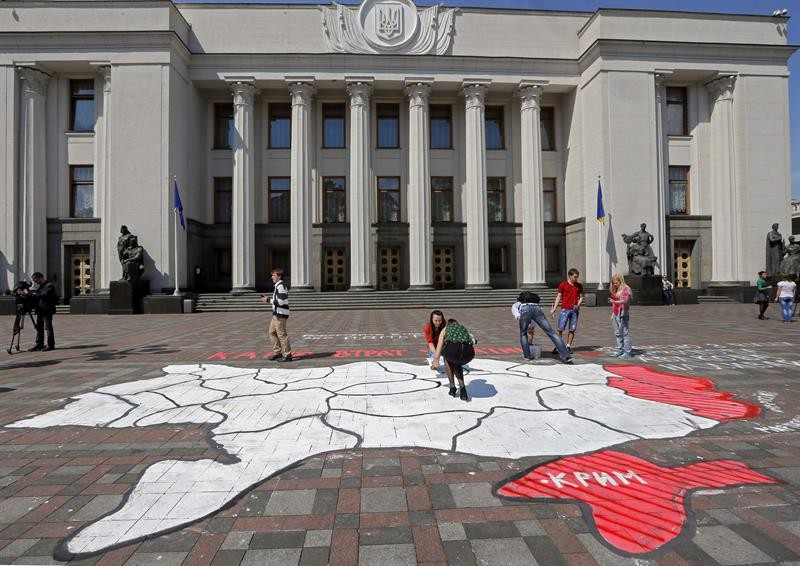 Ativistas ucranianos desenham um mapa do país, ressaltando em vermelho os territórios em disputa com os separatistas pró-russos, na frente do Parlamento de Kiev