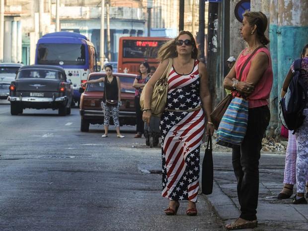 Mulher com vestido com as cores da bandeira dos EUA caminha nesta quinta-feira (17) pelo centro de Havana (Foto: YAMIL LAGE / AFP)