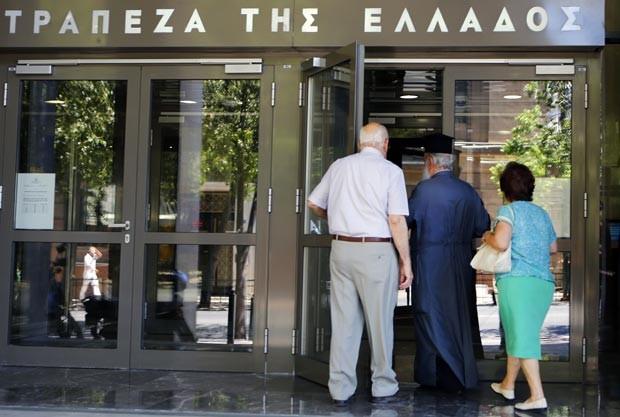 Gregos entram em agência bancária nesta quarta-feira (13) em Atenas (Foto: AFP)