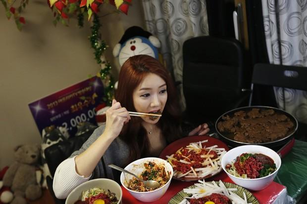 Park Seo-yeon come em frente à câmera enquanto transmite jantar para milhares de espectadores na Coreia do Sul (Foto: Kim Hong-Ji/Reuters)