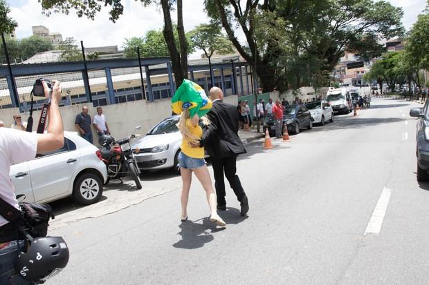 Ju Isen é levada por seu segurança (Foto: Divulgação)