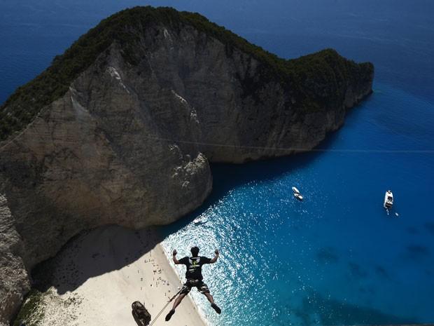 Praticante pula de penhasco em ilha da Grécia (Foto: Louisa Gouliamaki/AFP)