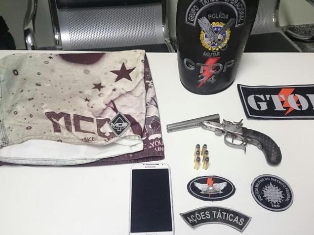 Itens apreendidos com suspeitos: arma, munição e celular da vítima de roubo em pizzaria no DF (Foto: Polícia Militar/Divulgação)