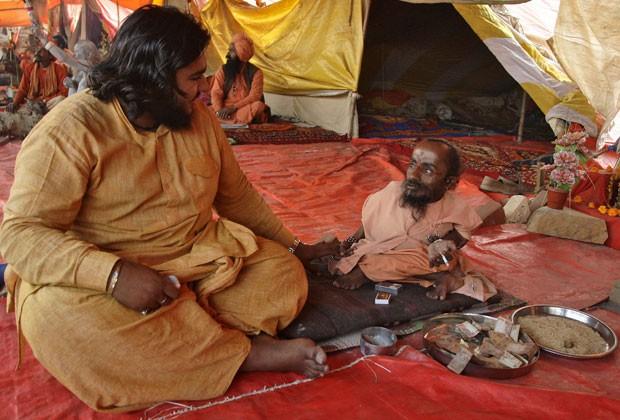 Mahadev Bharti conversa com colega em Allahabad; ele diz ser o homem mais baixo do mundo (Foto: Jitendra Prakash/AFP)