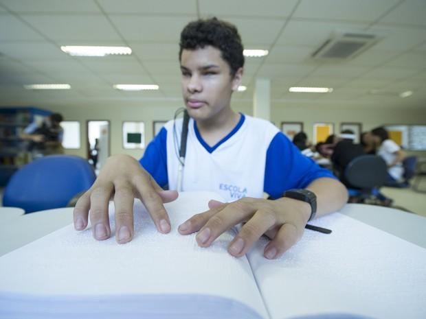 Estudante com deficiência visual lendo em braile (Foto: Divulgação/Sedu-ES)