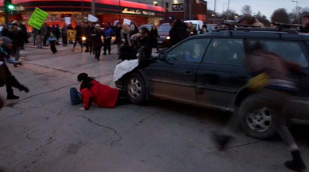 Um carro avançou contra manifestantes e atropelou uma mulher durante um protesto em Minneapolis em apoio à população de Ferguson nesta terça-feira (25) (Foto: The Star Tribune, Mark Vancleave/AP)