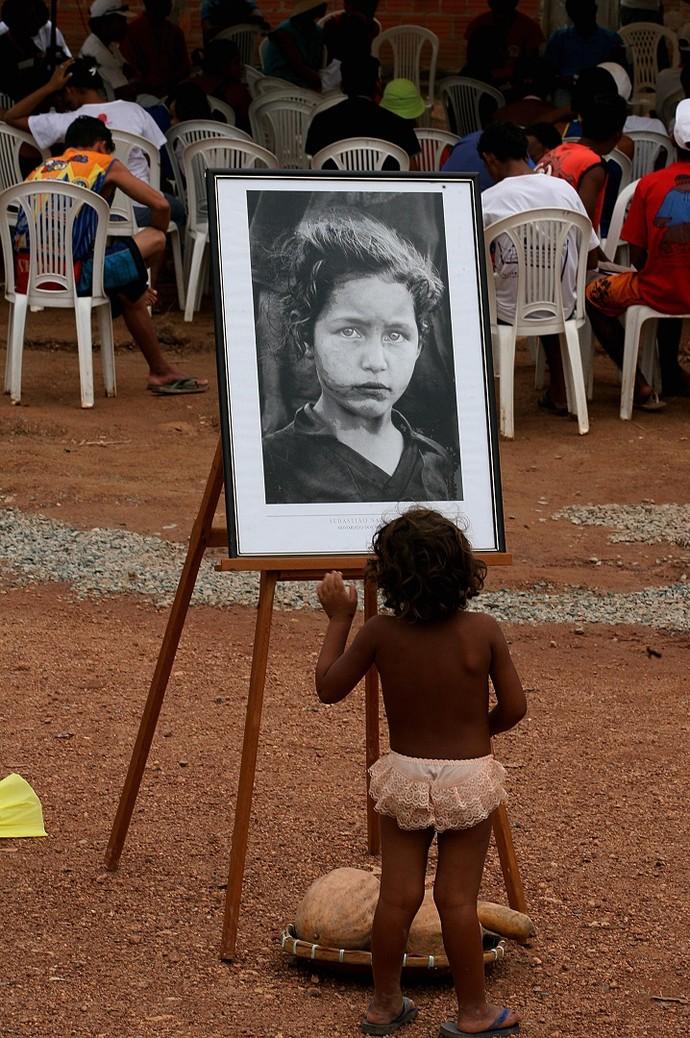 Criança observa uma das fotos de exposição de Sebastião Salgado (Foto: Jorge Araújo)