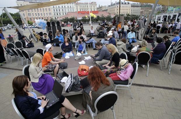 """Pessoas trabalham com seus notebooks ao ar livre durante o evento """"Working Everywhere"""" nesta sexta-feira (31), em Riga, capital da Letônia. (Foto: Ints Kalnins/Reuters)"""