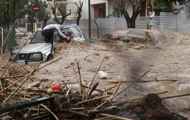 Enchente arrastou carros por rua de Chalandri nesta sexta-feira (22) (Foto: John Kolesidis/Reuters)