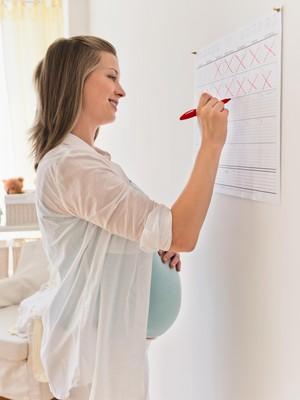 Mulher grávida contando dias no calendário (Foto: Tetra Images / Getty Images)
