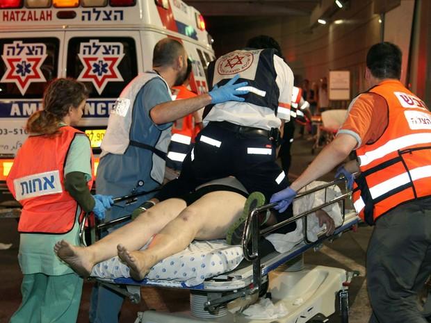 Equipe de emergência atende vítima de tiroteio nesta quarta-feira (8) em Tel Aviv (Foto: GIDEON MARKOWICZ / AFP)