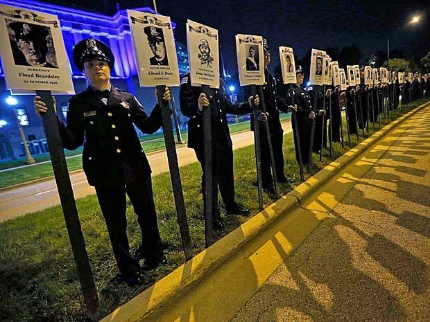 Policiais de Chicago, nos Estados Unidos, realizaram um ato em Illinois em memória dos colegas da corporação mortos durante o trabalho de combate ao crime. O grupo exibiu fotos dos oficiais que perderam a vida nas ruas. A manifestação ocorreu em Illinois, na noite desta terça-feira (16). Desde a formação do Departamento de Polícia de Chicago na década de 1830, 571 policiais morreram em cumprimento do dever. (Foto: Jim Young / Reuters)