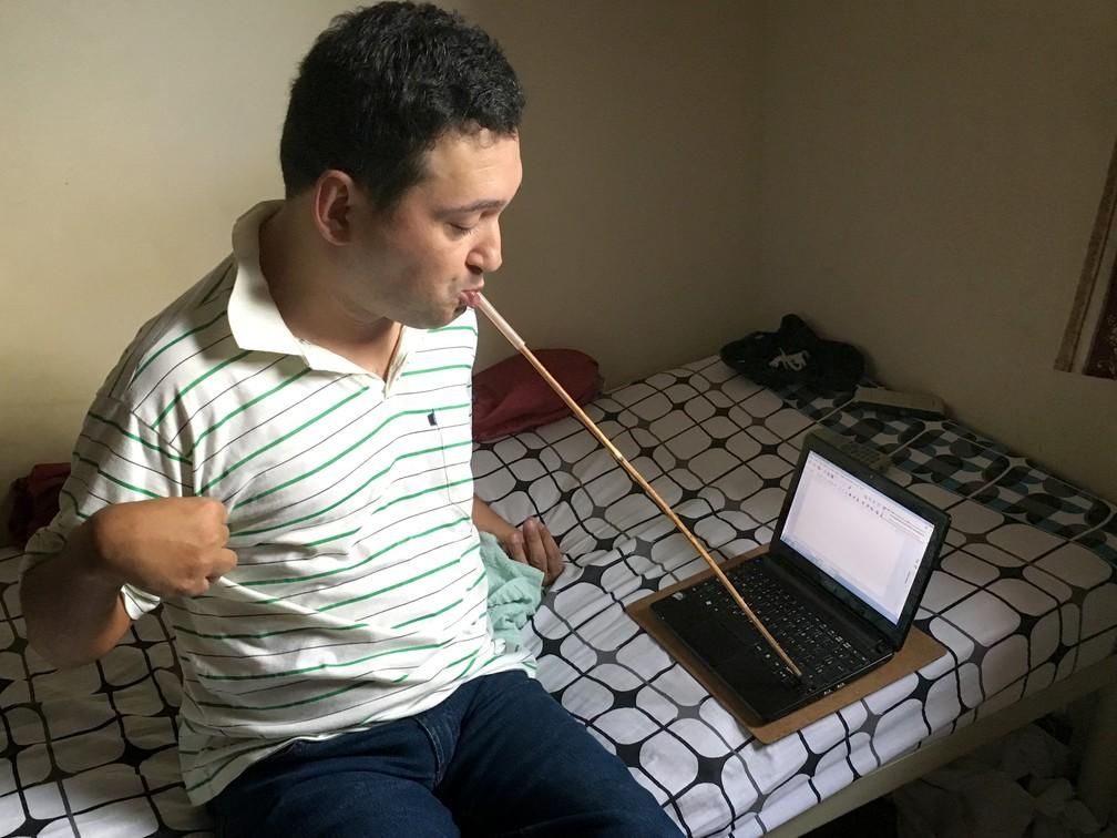 Fábio utiliza uma vareta de bambu para escrever seus poemas (Foto: Stephanie Fonseca/G1)