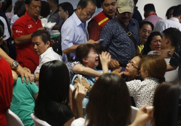 Familiares de vítimas do voo da AirAsia choram após saberem da localização dos destroços da aeronave nesta terça-feira (30) (Foto: Beawiharta/Reuters)