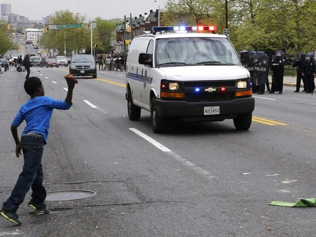 Policiais observam enquanto um garoto atira um tijolo em um carro da polícia em Baltimore, na segunda-feira (27) (Foto: AP Photo/Jose Luis Magana)