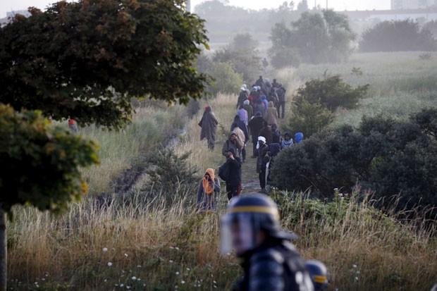 Imigrantes que estavam bloqueando o acesso de caminhões ao Eurotúnel são dispersados por policiais perto de Calais, na França, neste domingo (2) (Foto: Pascal Rossignol/Reuters)