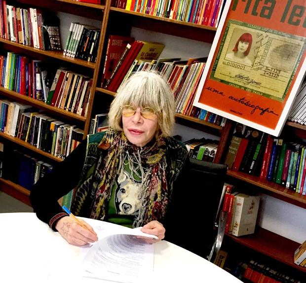 Rita Lee assina contrato para lançar sua autobiografia pela Globo Livros, com a capa ao fundo (Foto: Guilherme Samora)