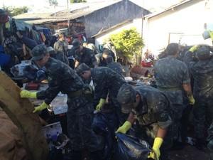 Agentes de saúde e voluntários do Exército participaram da limpeza do quintal da residência (Foto: Vanessa Navarro/RPC TV Londrina)