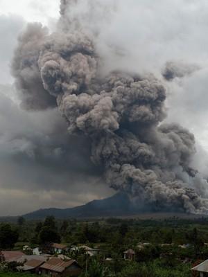 Vilarejo à frente do Monte Sinabung, na Indonésia, onde um vulcão em atividade forçou a saída de mais de 20 mil moradores (Foto: AFP / SUTANTA ADITYA)