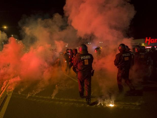 Policiais atravessam cortina de fumaça de sinalizadores atirados por manifestantes de extrema direita em Heidenau, na Alemanha, no sábado (22) (Foto: Reuters/Axel Schmidt)