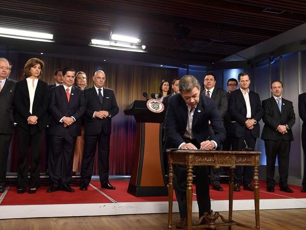O presidente da Colômbia, Juan Manuel Santos, assina decreto em que convoca oficialmente o plebiscito sobre acordo de paz com as Farc (Foto: Colombian Presidency/Handout via REUTERS)