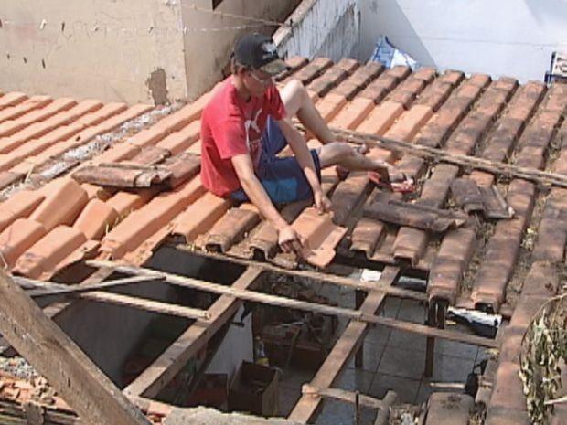 Morador arruma telhado destruído com queda do animal (Foto: Reprodução/TV TEM)