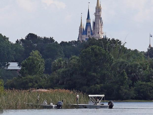 Agentes buscam o corpo de uma criança desaparecida em lago próximo ao castelo da Disney World em Orlando. Lane Graves, de 2 anos, foi arrastado para a água por um aligátor (jacaré americano) na lagoa Seven Seas, no hotel Disney's Grand Floridian Resort (Foto: Red Huber/Orlando Sentinel/AP)