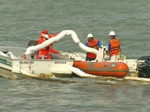 Equipes lança material usado para contenção do combustível marítimo que vazou no píer de São Sebastião, litoral norte de São Paulo. (Foto: Reprodução/TV Vanguarda)