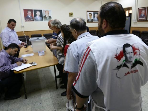 Sírios fazem fila em local de votação no centro de Damasco nesta terça-feira (3) (Foto: Louai Beshara/AFP)