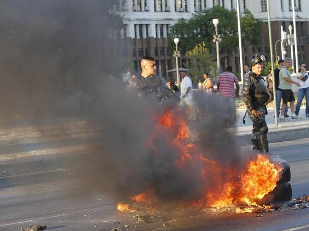 Policiais observam pneus incendiados na Avenida Presidente Vargas. Pelo menos 500 ativistas caminham, na tarde desta quinta-feira (06), pelas ruas do Centro do Rio de Janeiro, contra o aumento na tarifa dos ônibus (Foto: Onofre Veras/Agência O Dia/Estadão Conteúdo)
