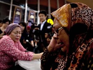 Parentes de passageiros do voo MH17 aguardam em área restrita do Aeroporto Internacional de Kuala Lampur, na Malásia (Foto: AFP PHOTO/ Manan Vatsyayana)