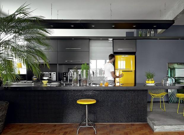 """""""Amarelo me faz bem."""" É com essa frase que o arquiteto Diogo Oliva olha para sua geladeira e justifica a escolha do tom. A cozinha teria tudo para ser sisuda: marcenaria e pastilhas pretas, cimento queimado. Mas ali está a cor (Foto: Victor Affaro/Casa e Jardim)"""