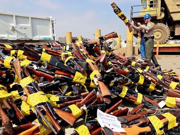 Um policial joga armas em uma grande pilha antes delas serem derretidas em uma usina siderúrgica de Rancho Cucamonga, na Califórnia. Cerca de 3400 armas confiscadas foram derretidas e o seu metal será utilizado na construção de estradas e pontes (Foto: Nick Ut/AP)