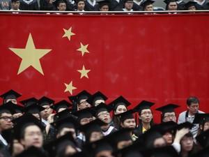 Alunos assistem ao lado da bandeira chinesa a cerimônia de graduação na Universidade de Fudan, em Xangai. (Foto: Aly Song/Reuters)