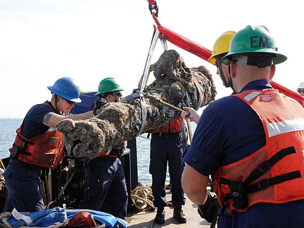 Membros da Guarda Costeira dos EUA erguem canhão de navio naufragado na costa da Carolina do Norte (Foto:  Karen A. Blum/NCDCR/AFP)