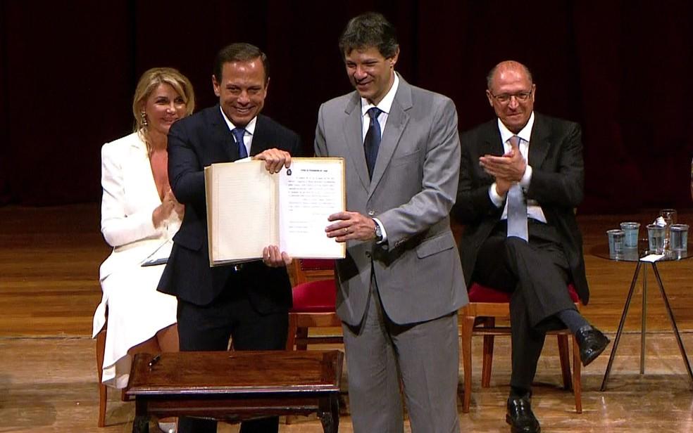 João Doria e Fernando Haddad mostram o documento de transmissão de cargo de prefeito (Foto: GloboNews/Reprodução)