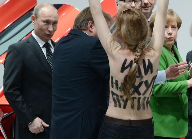 O presidente russo, Vladimir Putin (esq.), reage à aproximação da manifestante do Femen ao lado da chanceler alemã, Angela Merkel (dir.) (Foto: Jochen Lübke/DPA/AFP)