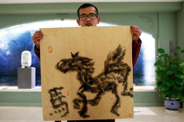 Han Xiaoming exibe obra pintada com a língua em Hangzhou (Foto: Aly Song/Reuters)