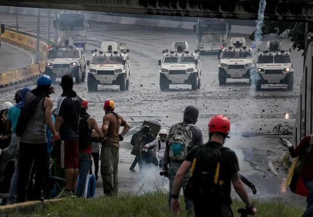 Manifestantes enfrentam as forças da Guarda Nacional em Caracas, em confronto que deixou um estudante morto (Foto: Miguel Gutiérrez/EFE)